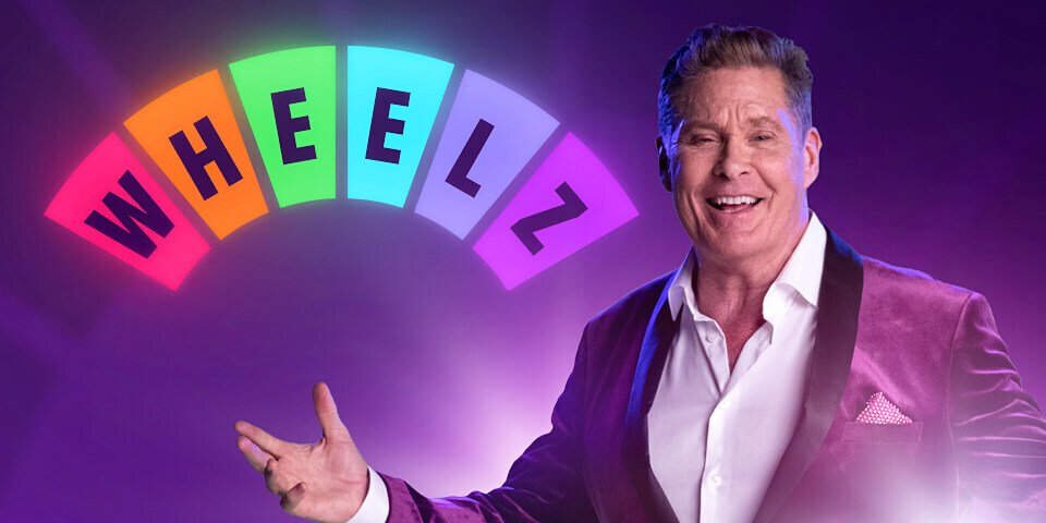 David Hasselhoff in Suit Presenting Wheelz Casino Logo